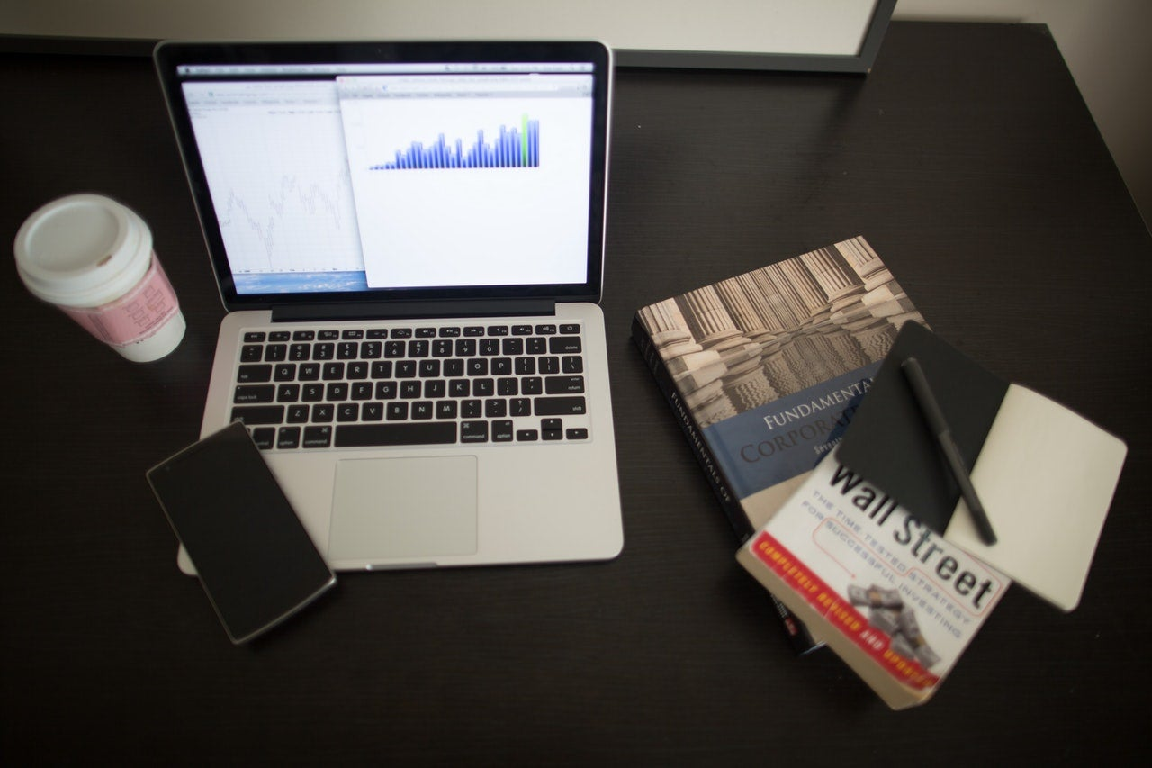 A laptop screen shows a bar chart of risky investments, and various investing books are next to the computer on a black tabletop.