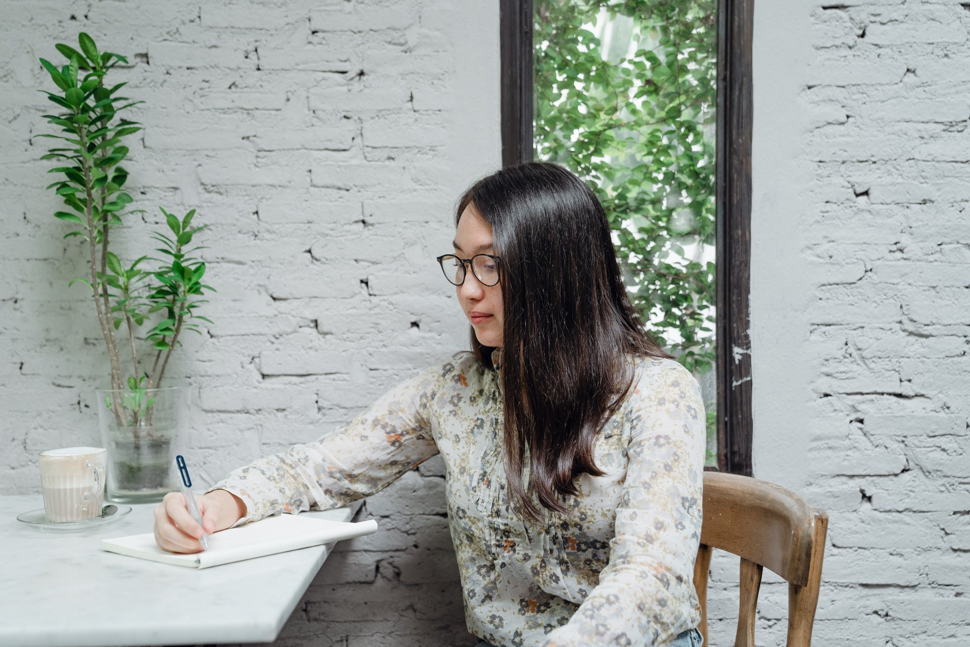 A young Asian woman sits at a tabletop writing in a notebook about how to budget for insurance.