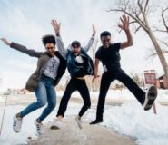 A group of young people jump in the air excitedly when they learn how secured credit cards can help their credit scores.