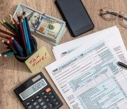 pens, a calculator and tax forms used for how to get a bigger tax refund
