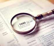 Magnifying glass on tax return, looking for taxpayer identity theft