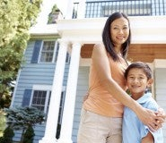 A woman and child stand smiling and embracing in front of a home.