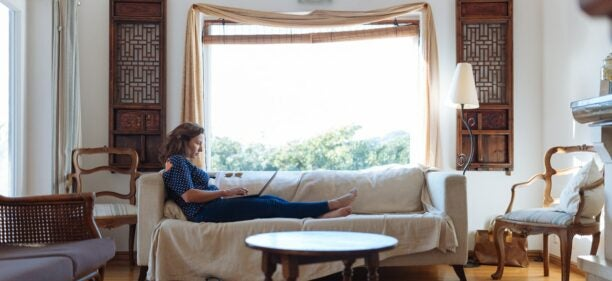 A woman in a gray shirt lounges on the couch in her rented apartment, checking her credit score on her laptop.