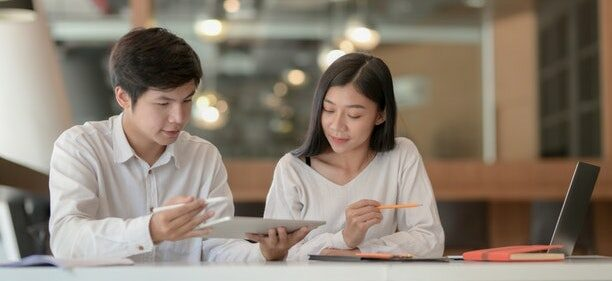 A man and a woman sit a table, looking on a tablet and discussing how to take control of finances.
