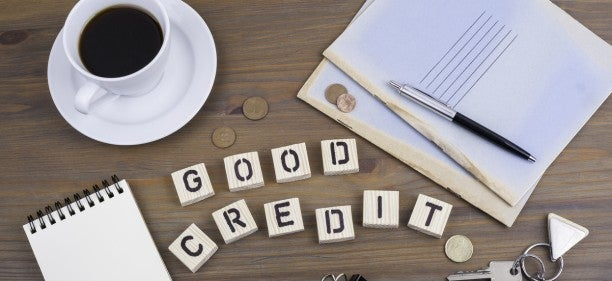 Good Credit spelled in scabble letters with copy cup and papers to s how you can improve credit score