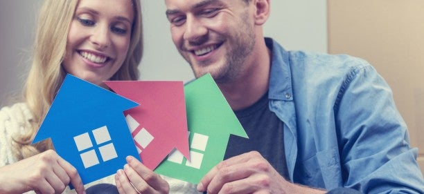 couple holding paper cut outs of houses happy because they are buying a house with bad credit