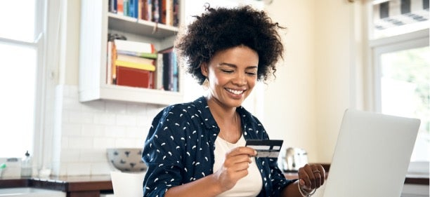 A woman holds her credit card and laptop,