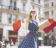 Woman on street swinging shopping bags--happy because she got the best credit card deals of 2019