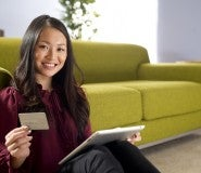 girl with laptop in front of couch holding best first credit card