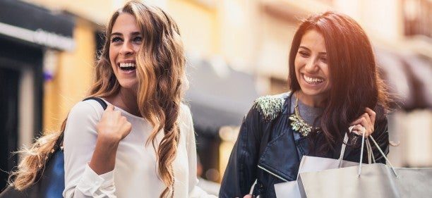 Two friends laughing and shopping.