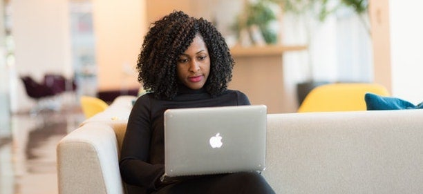 A woman sits on a couch scrolling on her laptop as she learns how to get a loan with bad credit.