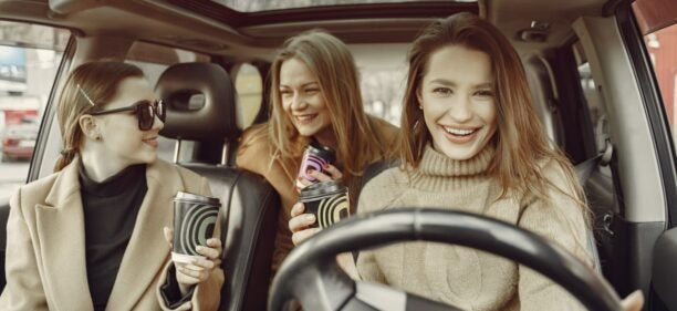 Three friends drive in a car, laughing and drinking coffee