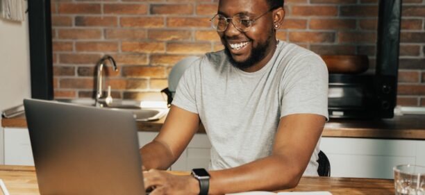 A young Black man with glasses and a gray tshirt sits at his kitchen counter smiling at his laptop learning how to maintain a 700 credit score with late payments.