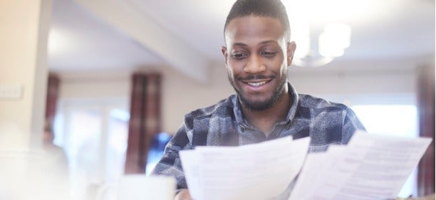 man smiling at his good debt to income ratio at he looks at his bank statements