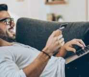 man on couch with laptop and credit card happy that he has the best credit card reward bonus