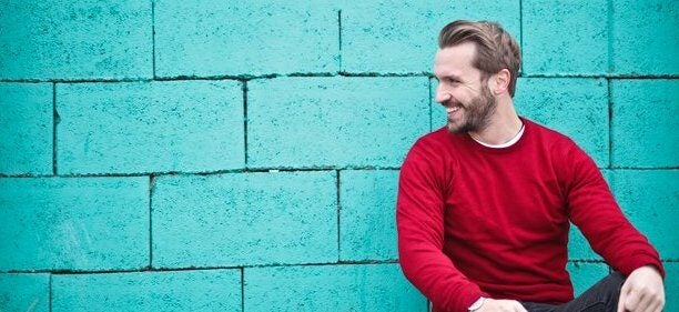 A man in a red sweater leans against a blue wall.
