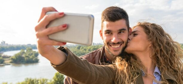 A woman kisses the cheek of a smiling man while taking a selfie of the two of them.