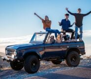 Three young people sit on top of a large offroad vehicle with their arms outstretched.