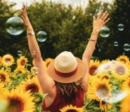 A woman in a straw hat stands in a field of sunflowers and bubbles with her back to the camera and her arms raised.