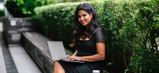 A smiling woman sits on a bench outside with her laptop.