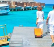 A man and a woman care suitcases on a pier, surrounded by water.