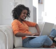 A woman sits on her grey sofa with her laptop on her lap.