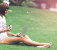 A woman sits on a grassy hill with a laptop on her lap and an OpenSky credit card in her hand.
